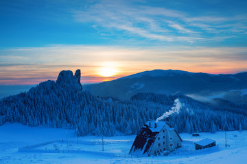 Caban in winter mountain on sunset with colorful background