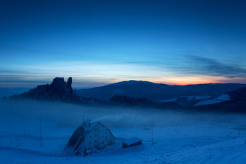 Caban in winter mountain on night