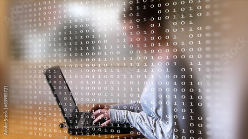 Woman typing on a laptop behind a frame full of computer code.