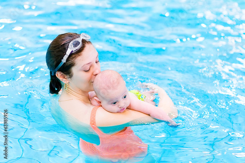 Litlte baby boy relaxing in a swimming pool with his mother