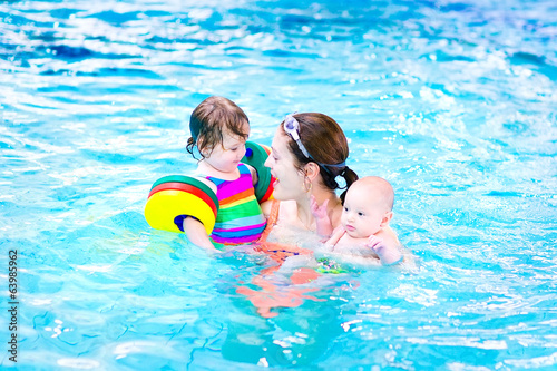 Young mother having fun in a swimming pool with her kids