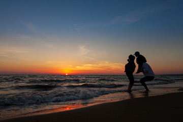 silhouette of happy family on the beach at sunset