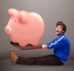 Handsome man holding a huge savings piggy bank
