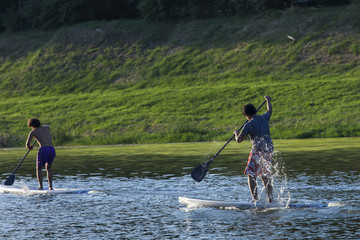 Men paddleboarding at sunset, Florence river, Italy, recreation