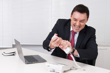 Angry business man screaming at phone in his office