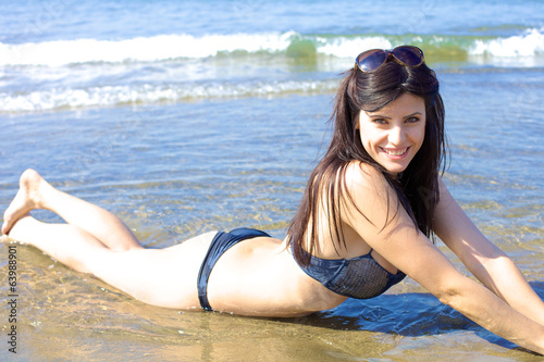 Cute female model smiling happy laying on seaside