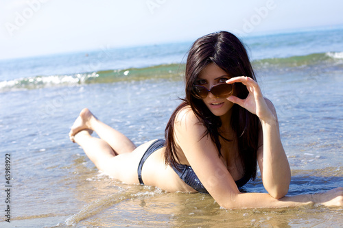 Happy female model with sun glasses playing in water