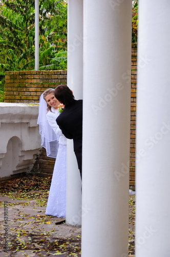 The bride and groom look out from behind a pillar