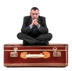 manager seduto sopra una valigia