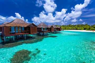 Over water bungalows with steps into green coral lagoon