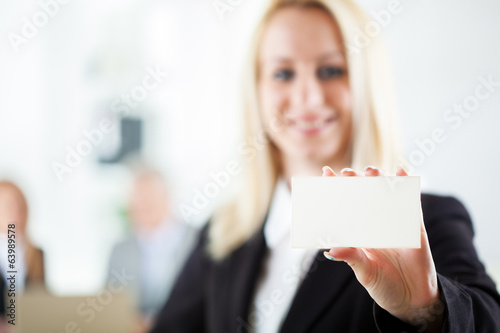 Beautiful young businesswoman holding Blank business card