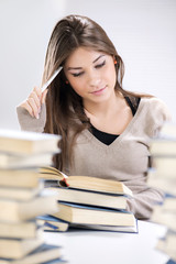 Beautiful girl learning and thinking between many books.