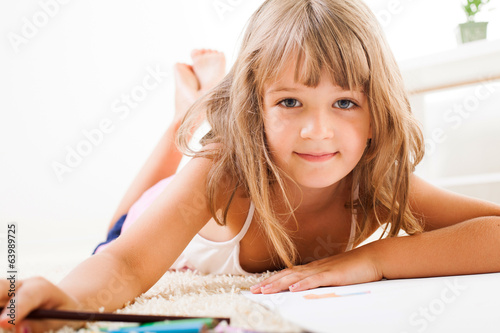 Cute little girl with color crayons lying on the floor