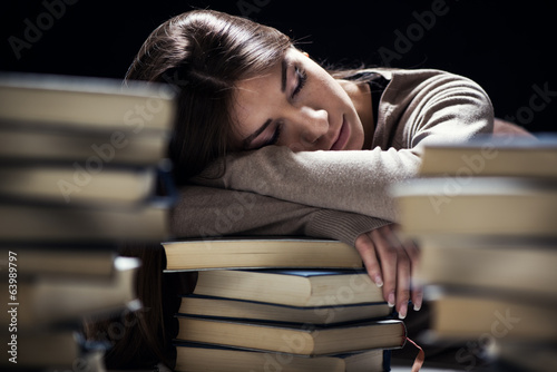 Tired student fell a sleep between many books