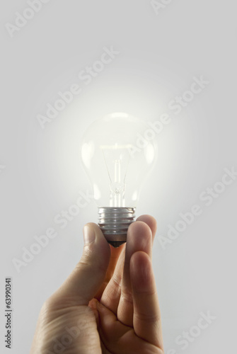 holding light bulb isolated on white