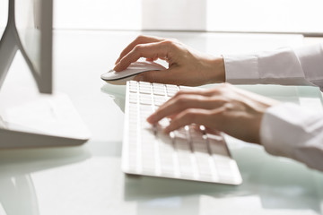 Close-up of hands woman using a mouse and keyboard computer