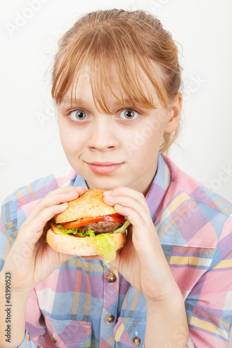 Little blond girl with homemade burger on white background