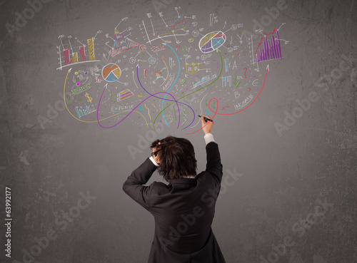 Young business man looking at sketches of graphs and symbols