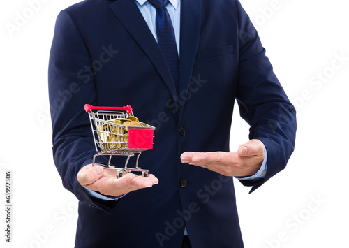 Businessman showing trolley with gold coin