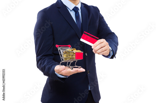 Businessman holding shopping cart with golden coin and credit ca