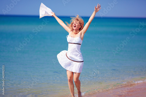 happy girl jumping on summer beach