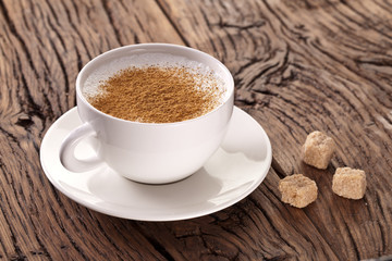 Cup of cappuccino with ground cinnamon.