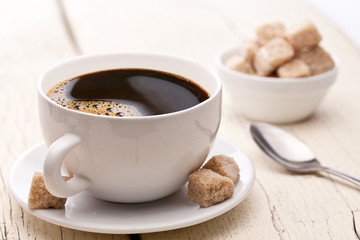 Cup of coffee with sugar cubes.