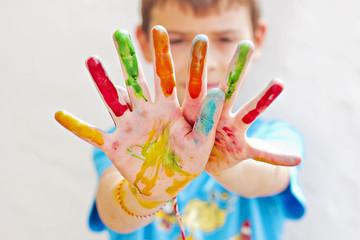 Niño con manos pintados de colores