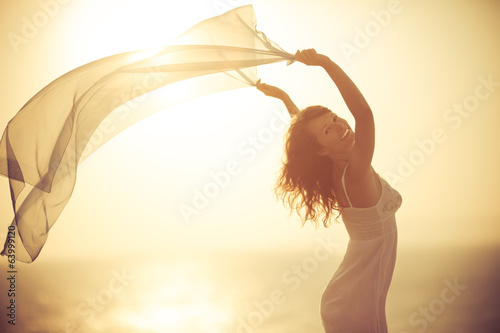 Silhouette of young woman relaxing at the beach
