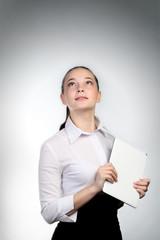 молодая девушка с планшетом в руках смотрит над головой