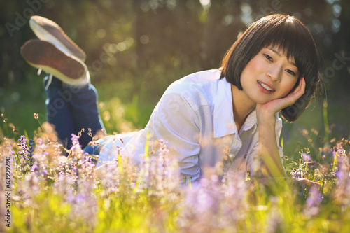 Beautiful asian girl relaxing among flowers
