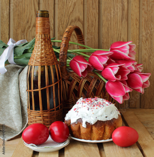 Easter cake, tulips in a basket and colored eggs.