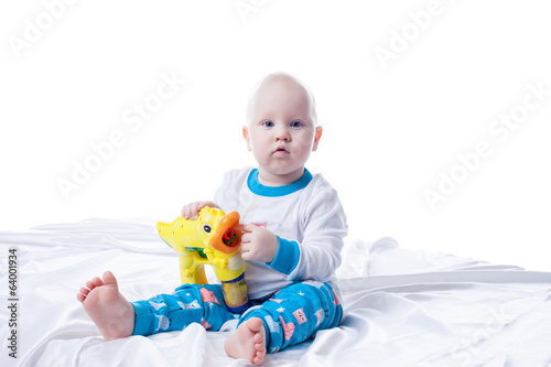 Cute little boy playing with toy in studio
