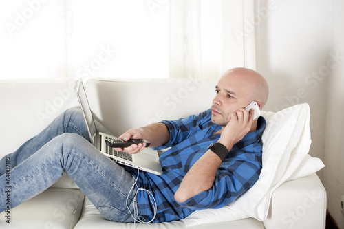 young man multi tasking on computer, mobile phone and remote tv