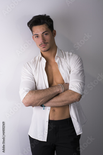 Attractive young man with white shirt open on naked torso