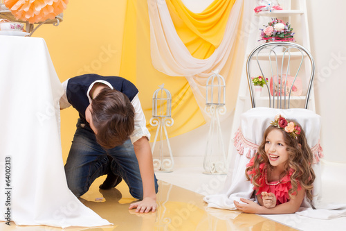 Image of brother and sister play hide-and-seek