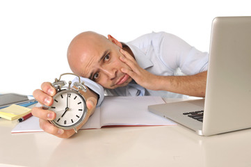exhausted bald business man with computer and alarm clock