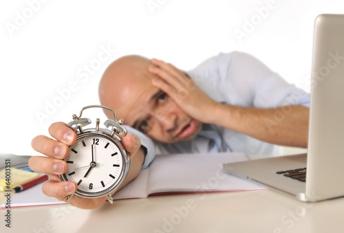 tired bald business man with computer and alarm clock