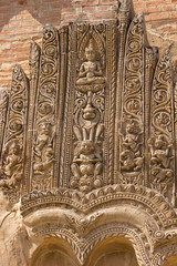 old sloughing bas-relief with religious ornament on the facade o