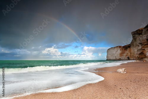 rainbow over ocean coast by cliff