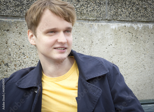 Handsome young man sitting on a bench smiling. Candid.