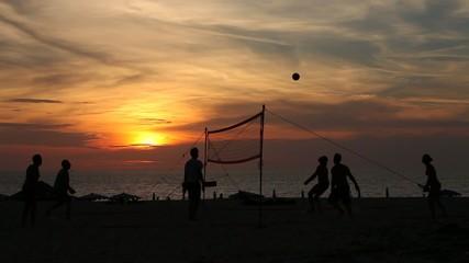 Люди играют в волейбол на пляже вечером