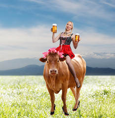 Tiroler or oktoberfest woman with beer sitting on a cow
