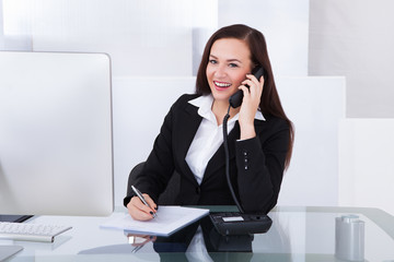 Businesswoman Using Telephone At Desk