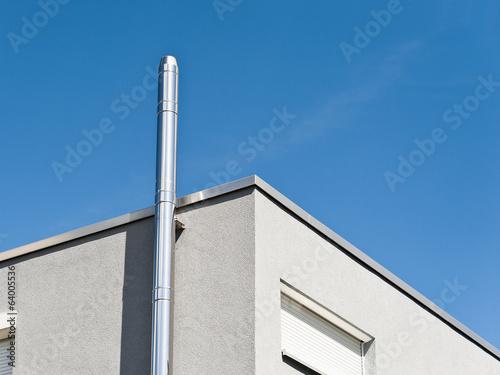 Ein Schornstein aus Edelstahl an einem modernen Gebäude - 64005536
