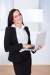 Welldressed Businesswoman Using Laptop In Office