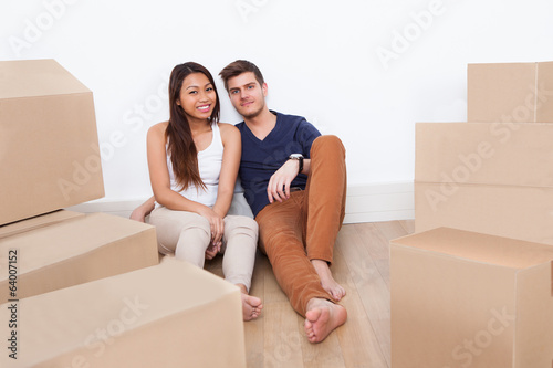 Couple Sitting On Floor At New Home