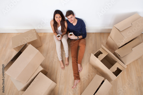 Couple Having Coffee On Floor In New Home