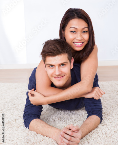 Portrait Of Loving Couple Lying On Rug