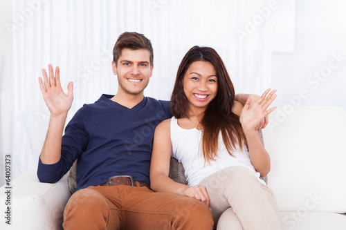 Couple Waving While Sitting On Sofa